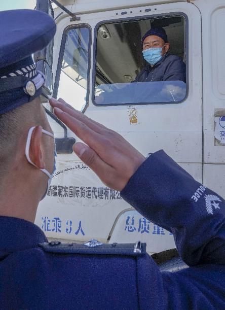 在新疆卡拉苏口岸,卡拉苏出入境边防检查站警官杨开祥向出境车辆驾驶员敬礼(10月16日摄)。