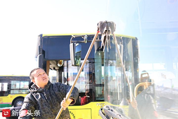 郭刚正在擦洗104路公交车的玻璃。