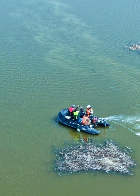 2020年4月3日,湿地管护人员与村民一起乘坐小船在新疆昌吉州呼图壁县五工台镇百泉湖湿地进行巡查。(陶维明 摄)