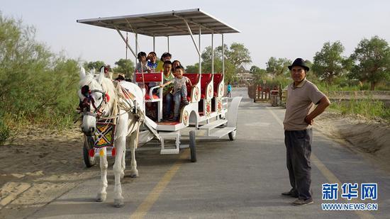 罗布人村寨村民阿吾力·巴西提和他的马车。新华网 董亚倩摄