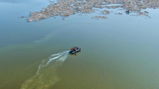 2020年4月3日,湿地管护人员与村民一起乘坐小船在新疆昌吉州呼图壁县五工台镇百泉湖湿地进行巡查,清理水面漂浮垃圾。(陶维明 摄)