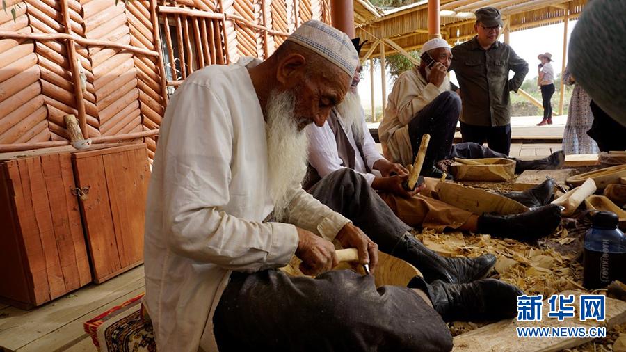 罗布人村寨百岁老人在制作卡盆模型。新华网 董亚倩摄