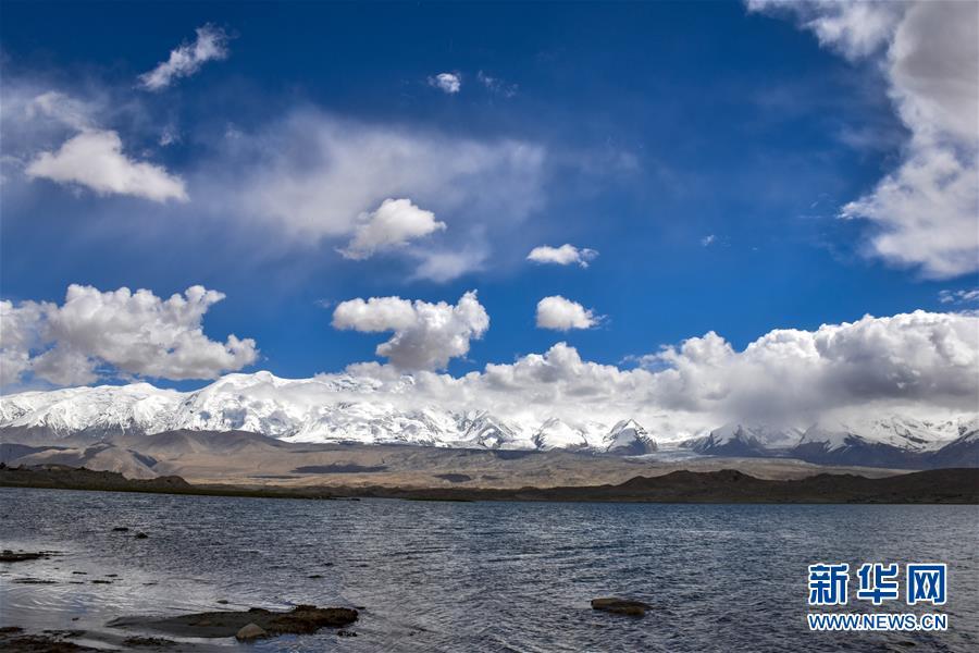 帕米尔高原上喀拉库勒湖畔连绵的雪山(6月16日摄)。