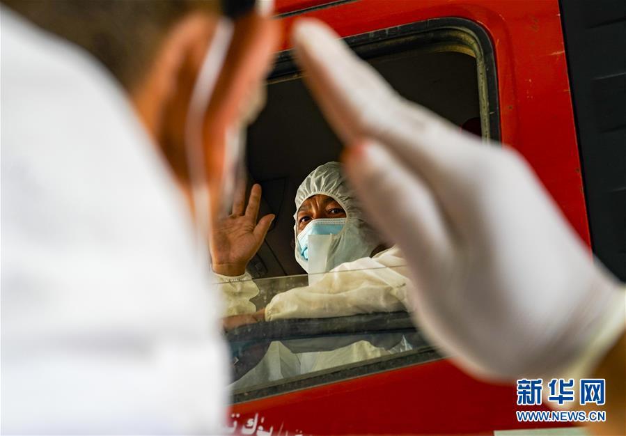 8月16日,在乌鲁木齐市高新区(新市区)一处执勤点,高新区(新市区)交警大队执勤民警向运送防疫物资的司机敬礼。新华社记者 赵戈 摄 乌鲁木齐:守护疫情防控绿色通道