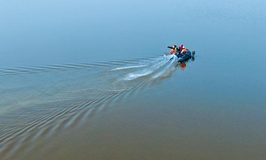 2020年4月3日,湿地管护人员与村民一起乘坐小船在新疆昌吉州呼图壁县五工台镇百泉湖湿地开展巡查工作。(陶维明 摄)