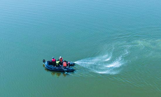 2020年4月3日,湿地管护人员与村民一起乘坐小船在新疆昌吉州呼图壁县五工台镇百泉湖湿地对水面漂浮垃圾进行清理。(陶维明 摄)