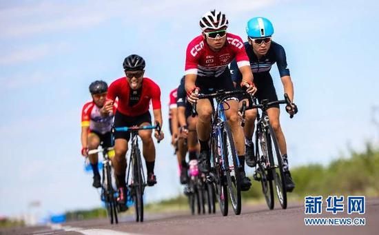 第十三届环赛里木湖公路自行车赛第一赛段中车手们沿路骑行。于苏甫·艾尼摄