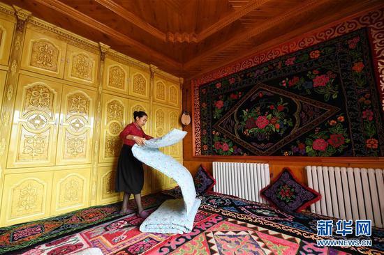 5月23日,在新疆新源县那拉提镇阿尔善村,居玛古丽·艾地巴依在收拾家务。新华社记者贺灿铃摄
