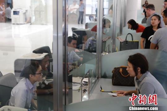 资料图:上海市公安局出入境管理局内,民众正在咨询和办理相关业务。 殷立勤 摄
