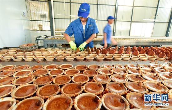 云南省弥勒市竹园镇那俺村竹诚食品厂工人正在忙着制作红糖。新华网发(普佳勇1月2日摄)