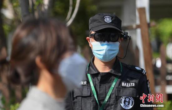 资料图:一位安保人员通过智能AR眼镜为游客测体温。中新社记者 王刚 摄