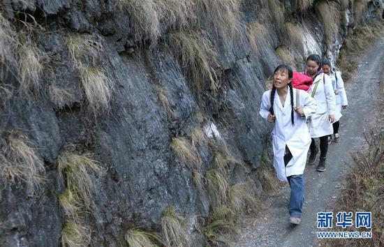 在云南怒江贡山县丙中洛镇,管延萍(左)与同事走在进村的山路上(1月13日摄)。