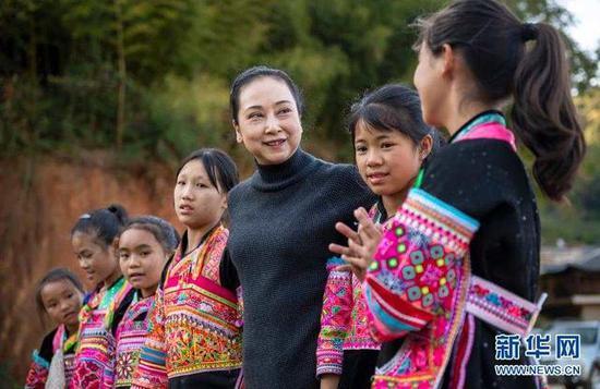 11月21日,张萍(右三)和孩子们一起走在那夺村里。