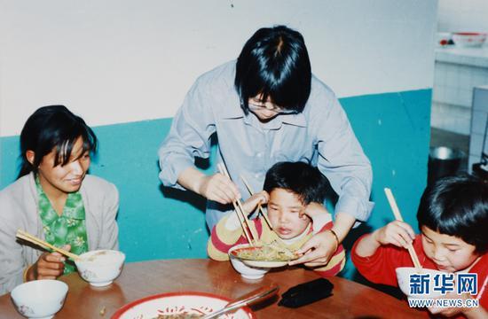 """2002年,张桂梅在""""儿童之家""""照顾孩子们吃饭(资料图)。新华网发(华坪县融媒体中心 供图)"""