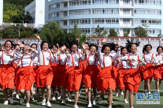 丽江华坪女子高级中学,学生们面对镜头欢快地招手(2019年10月16日摄)。新华网 赵普凡 摄