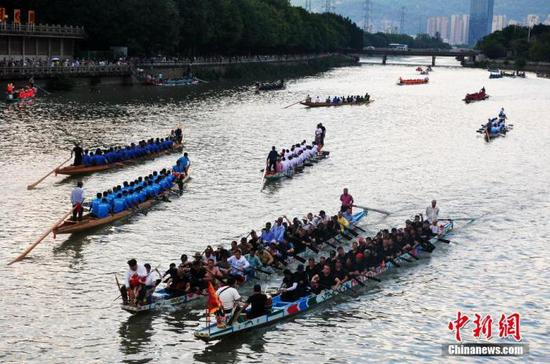 6月13日,福建福州,民众在光明港河道上划龙舟迎端午。 中新社记者 张斌 摄