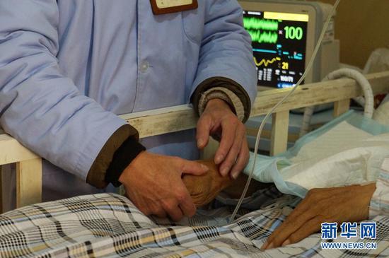 图为护工照顾老年患者。(新华网 潘越 摄)