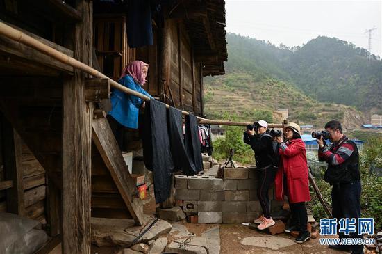 """4月7日,在板江村参与""""民艺游学计划""""的三位成都摄影师在拍摄村民李乜修制作传统草木染麻布的过程。新华社记者 江宏景摄"""