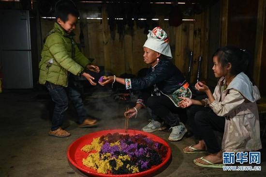 4月7日,板江村村民陆的刀(中)把煮熟的彩色米饭分给小朋友吃。新华社记者 江宏景摄