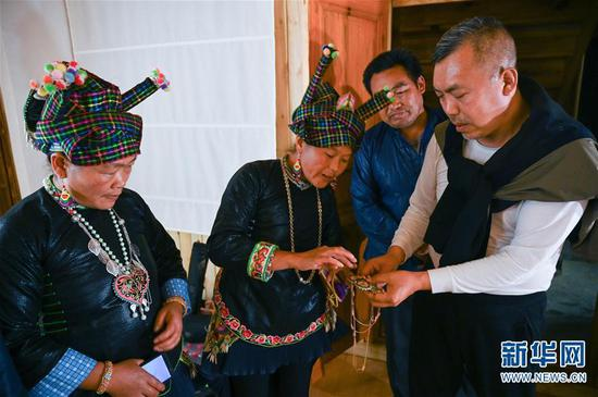 4月6日,成都摄影师金平在听板江村村民王文莲(左二)介绍传统壮族刺绣。 新华社记者 江宏景摄