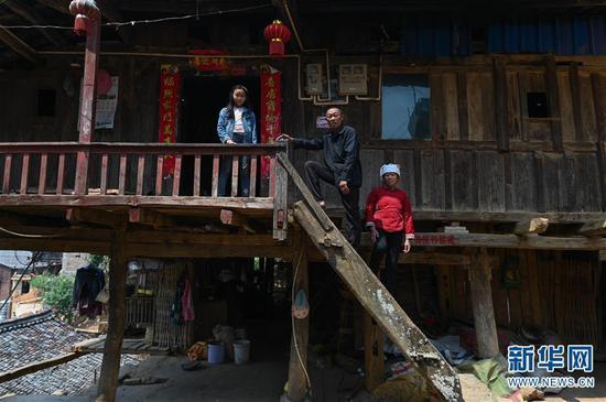 4月6日,板江村村民陆光明(中)与妻子、女儿站在自家房屋前。新华社记者 江宏景摄