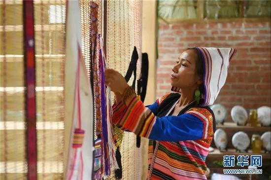 景洪市基诺山基诺族乡巴飘村村民姿梅在整理出售的传统手工织物(2019年6月10日)。新华社记者 秦晴 摄
