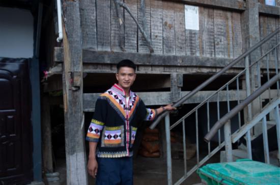 云南勐海县布朗山乡曼囡村,22岁的拉祜族青年扎培在自家门前。(贾翔 摄)