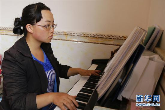 合唱团成员龙俊美在弹钢琴。新华网 罗春明 摄