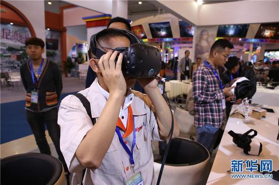 南博会上参观者正在智慧旅游区体验新产品。 (新华网 罗春明 摄)