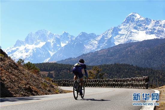 选手骑行览玉龙雪山风光。 新华网 张翼鹏 摄