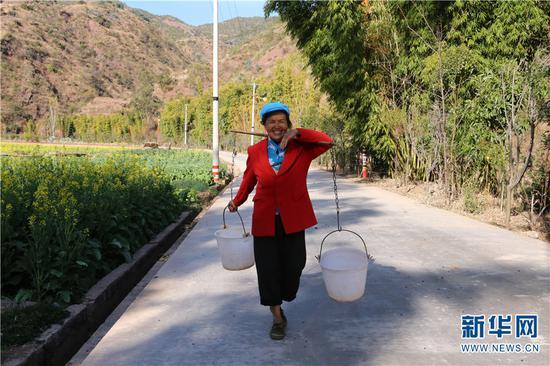 图为祥云县下庄镇金旦村一位村民走在新建成的环村路上。