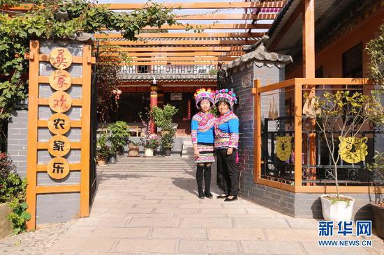 图为张志华(左)与母亲在自家农家乐门前。