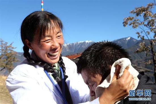 在云南怒江贡山县丙中洛镇小查腊村,管延萍(左)为村民学罗军洗头(1月14日摄)。