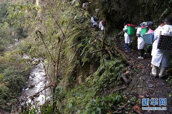 在云南怒江贡山县丙中洛镇,医疗队员在山间道路上前行(1月12日摄)。
