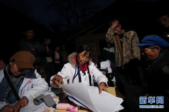 在云南怒江贡山县丙中洛镇碧汪村,管延萍(左二)在手电筒的灯光下为村民夜诊(1月12日摄)。