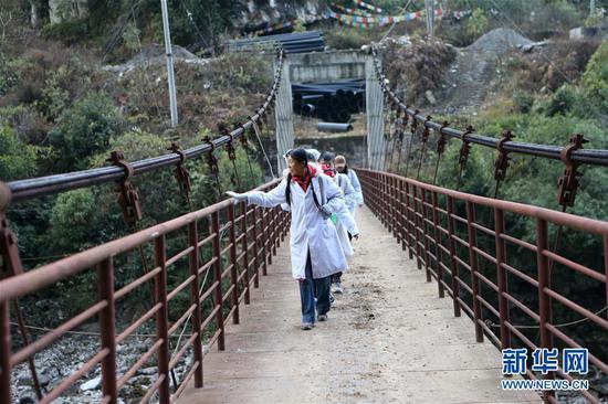 在云南怒江贡山县丙中洛镇,管延萍(前)与同事步行通过怒江(1月12日摄)。