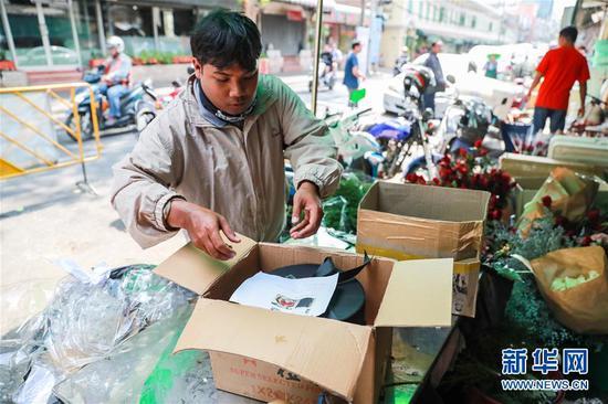 2月14日,在泰国曼谷帕空鲜花市场的一家花店,快递人员将由云南鲜花制作成的花盒取走配送。 新华社记者 张可任 摄