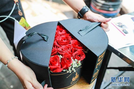 2月14日,在泰国曼谷帕空鲜花市场的一家花店,工作人员将从云南进口的鲜花制作成花盒。 新华社记者 张可任 摄