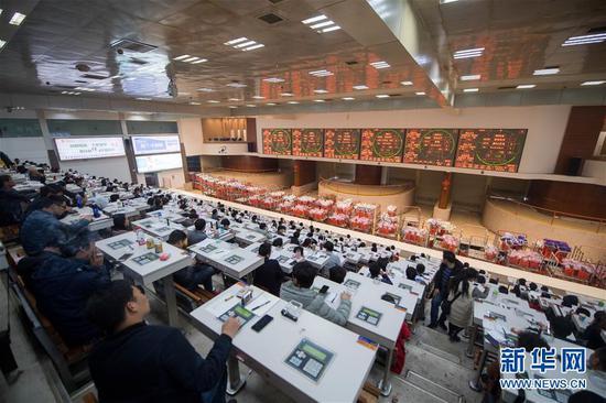 2月12日,花商在中国云南昆明斗南国际花卉拍卖交易中心内竞拍各种鲜花。 新华社记者 江文耀 摄
