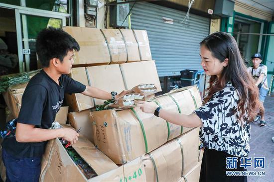 2月10日,在泰国曼谷,锦泰花卉的店主马娜(右)检查刚刚到货的云南鲜花。 新华社记者 张可任 摄