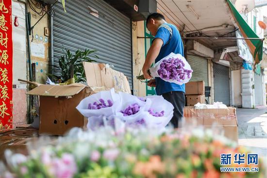 2月10日,在泰国曼谷,锦泰花卉的工作人员将从云南进口的鲜花进行初步处理。 新华社记者 张可任 摄