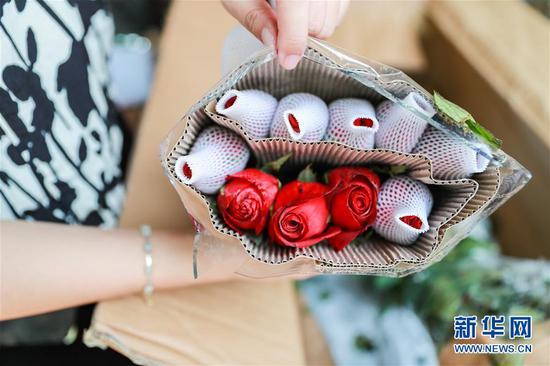 2月10日,在泰国曼谷,锦泰花卉的店主马娜检查刚刚到货的云南鲜花。 新华社记者 张可任 摄