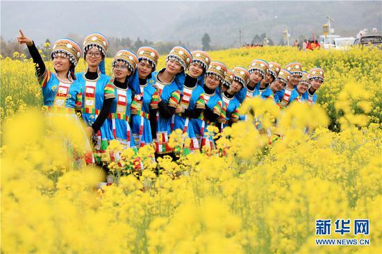 妇女们相约油菜花海欢度节日。新华网发 (李黎 摄)
