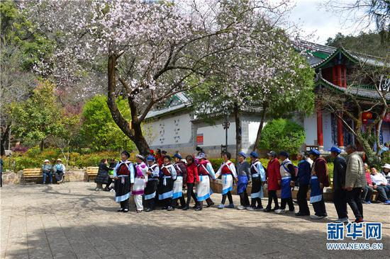 丽江黑龙潭公园里,人们载歌载舞。