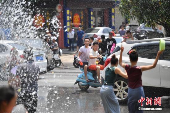 4月13日,街头充满欢乐的气氛。当日,在云南省德宏傣族景颇族自治州瑞丽市,泼水节欢乐依然在持续,民众相约走上街头泼水狂欢。中新社记者 刘冉阳 摄