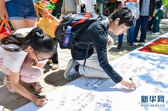 参与者在长卷上签名。徐华陵 摄