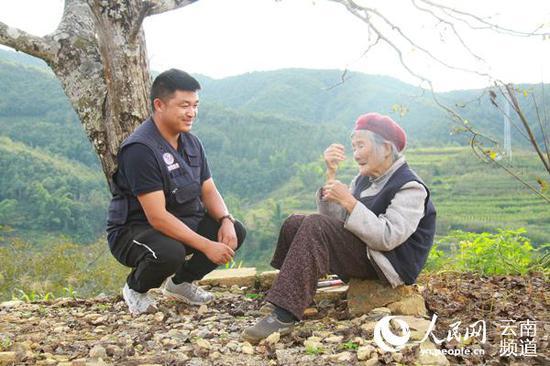 戴学江上前问候坐在村头树下晒太阳的老人。(人民网 符皓 摄)