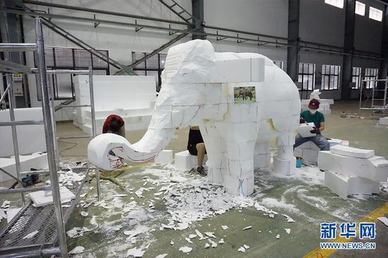 图为制作团队正在打磨小象。供图 新华网发