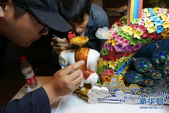 李耀辉(右)和同事正在制作彩车小样模型。供图 新华网发