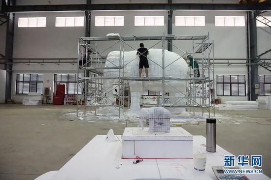 图为制作团队正在车间制作泡沫大象。供图 新华网发